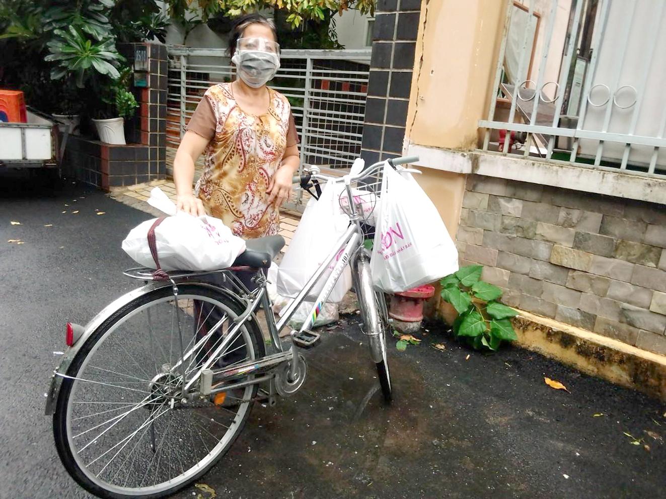 Chị Dương Thị Kim Cúc làm shipper đi chợ giúp dân bằng chiếc xe đạp