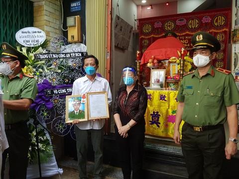 Thiếu tướng Lê Hồng Nam trao Huân chương và Quyết định truy thăng quân hàm cho đại diện gia đình đồng chí Phan Tấn Tài. Ảnh: CA