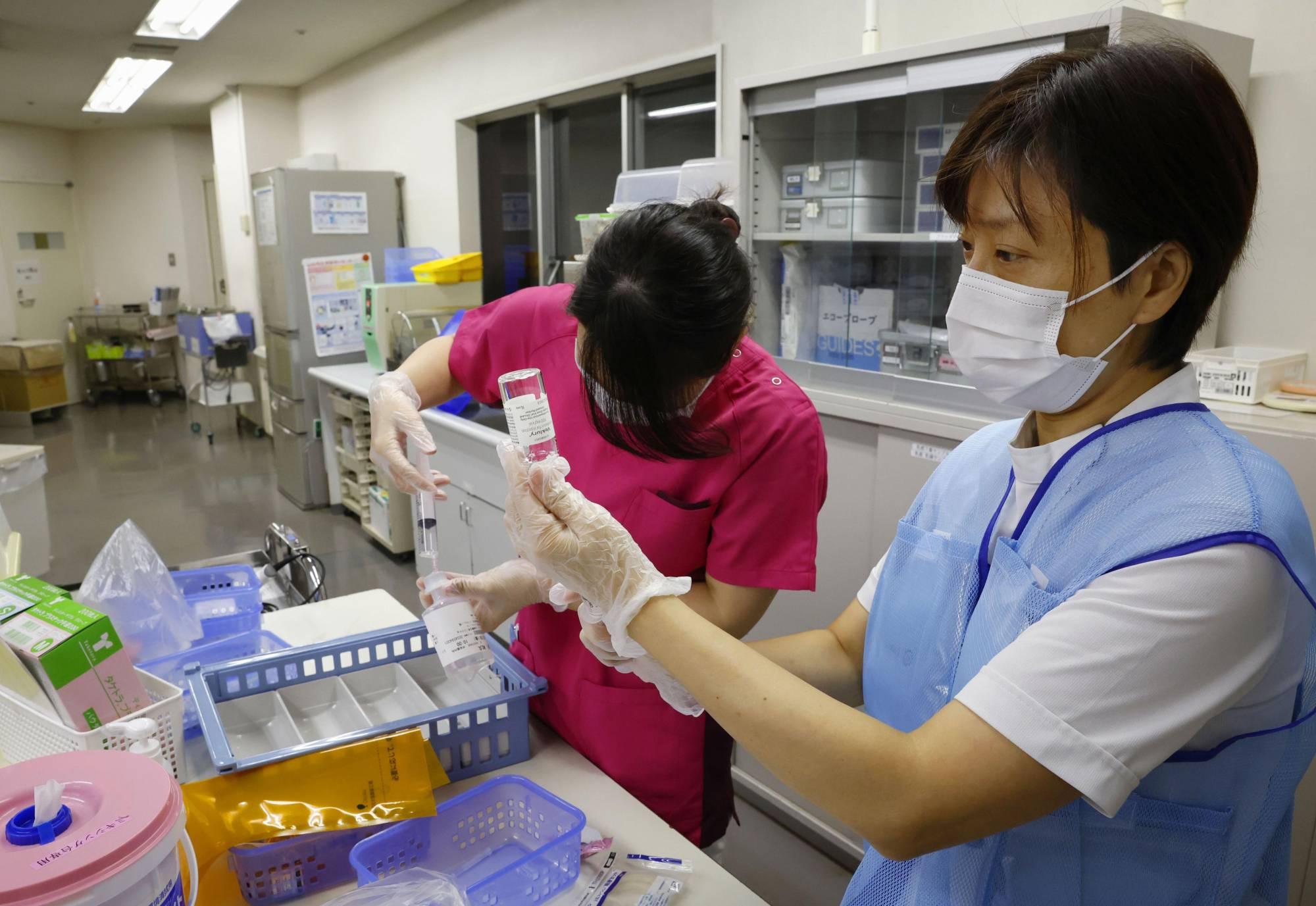 Các y tá chuẩn bị thuốc cho một bệnh nhân COVID-19 tại Bệnh viện Yokohama Rosai.