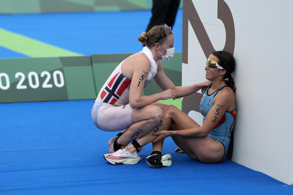Claire Michel (Bỉ) nhận được hỗ trợ và an ủi của Lotte Miller (Na Uy) sau khi kết thúc cuộc thi ba môn phối hợp cá nhân nữ - hình lan tỏa tinh thần Olympic tại Tokyo, Nhật Bản. Ảnh: AP