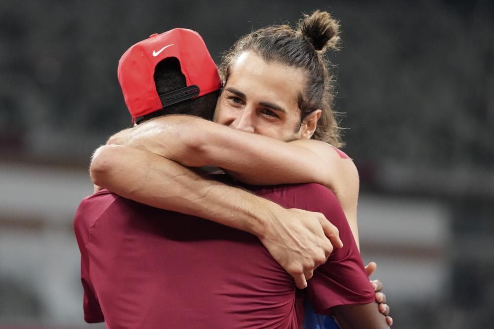 Gianmarco Tamberi (Ý) ôm lấy người cùng giành huy chương vàng Mutaz Barshim (Qatar) với mình sau trận chung kết nhảy cao nam tại Thế vận hội mùa hè 2020 ở Tokyo. Ảnh: AP