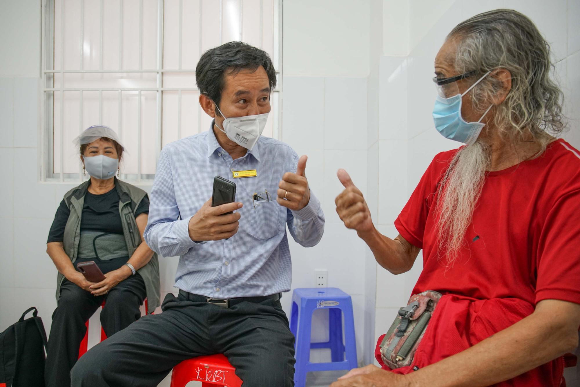 BS-CK2 Trần Văn Khanh, Giám đốc Bệnh viện Lê Văn Thịnh (TP Thủ Đức), ân cần thăm hỏi cụ bác Lê Thăng (82 tuổi) sau khi tiêm.
