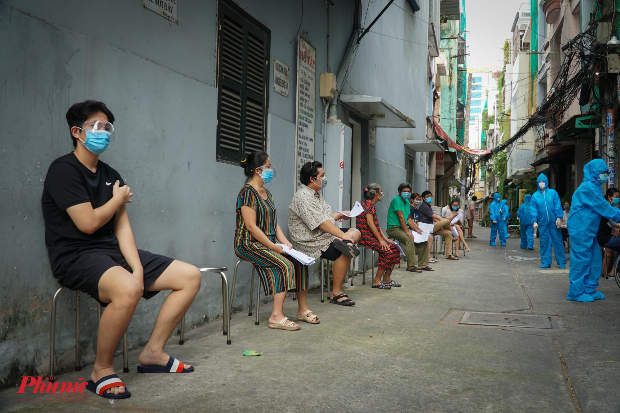 Sau khi tiêm, người dân ngồi chờ giãn cách, theo dõi sức khỏe ít nhất 15 phút