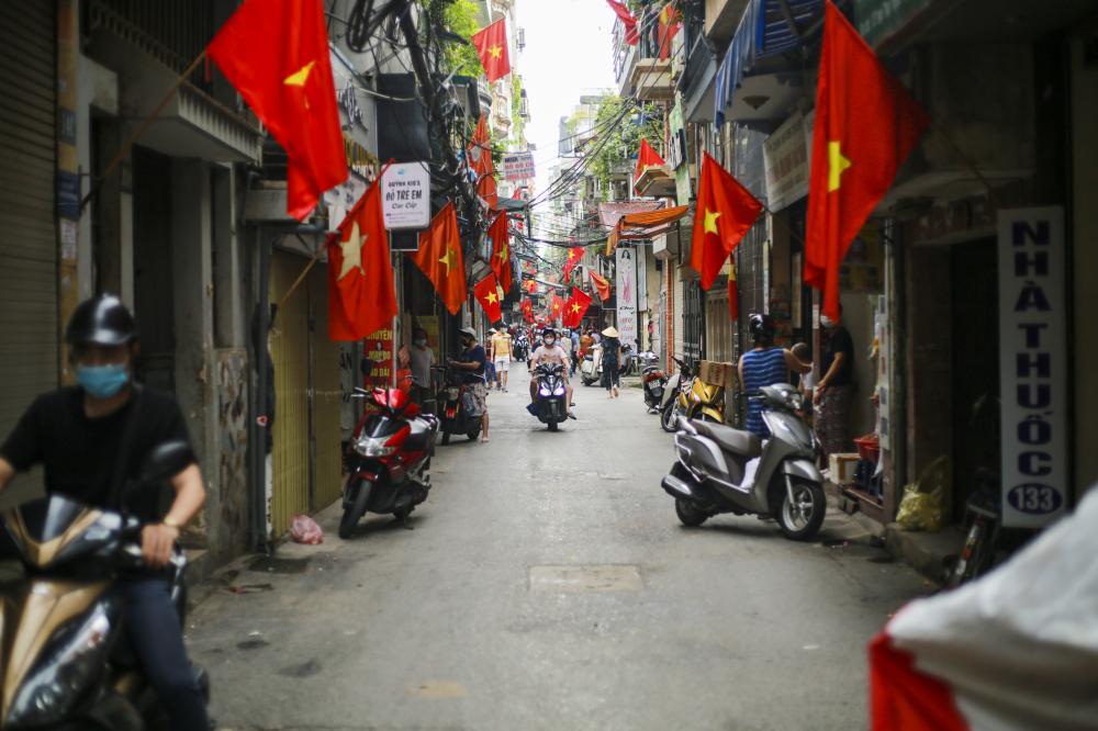 Người dân tại Hà Nội trang trọng cắm lá cờ Tổ quốc trước cửa nhà để chào mừng kỷ niệm 76 năm Quốc khánh 2/9.