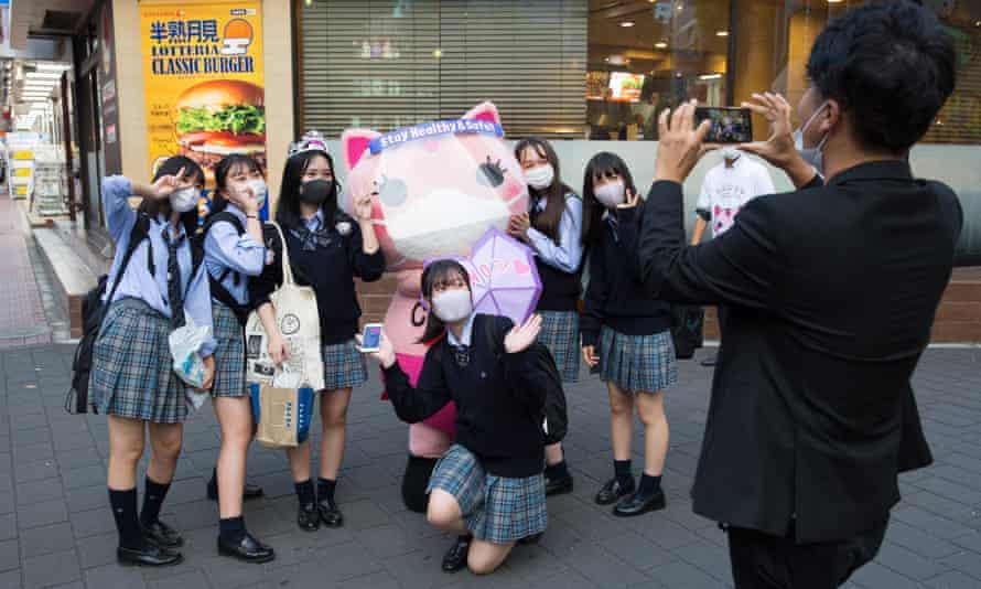 Koronon, một linh vật mèo chống coronavirus Nhật Bản chụp ảnh với một nhóm nữ sinh đeo khẩu trang ở Ikebukuro, Tokyo