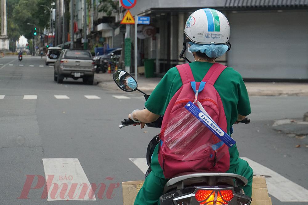 Nữ nhân viên y tế mang chiếc ba lô cùng kính chắn trên đường đi chi viện