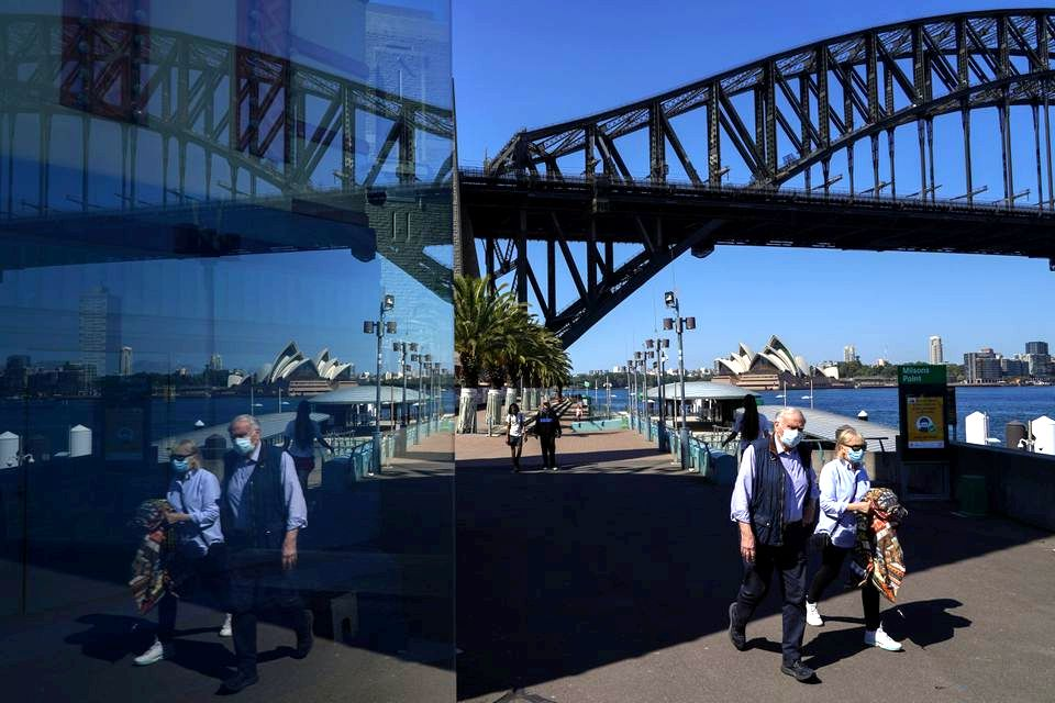 Những người đeo khẩu trang đi qua Cầu Cảng Sydney hôm 3/9, trong giai đoạn giãn cách của thành phố