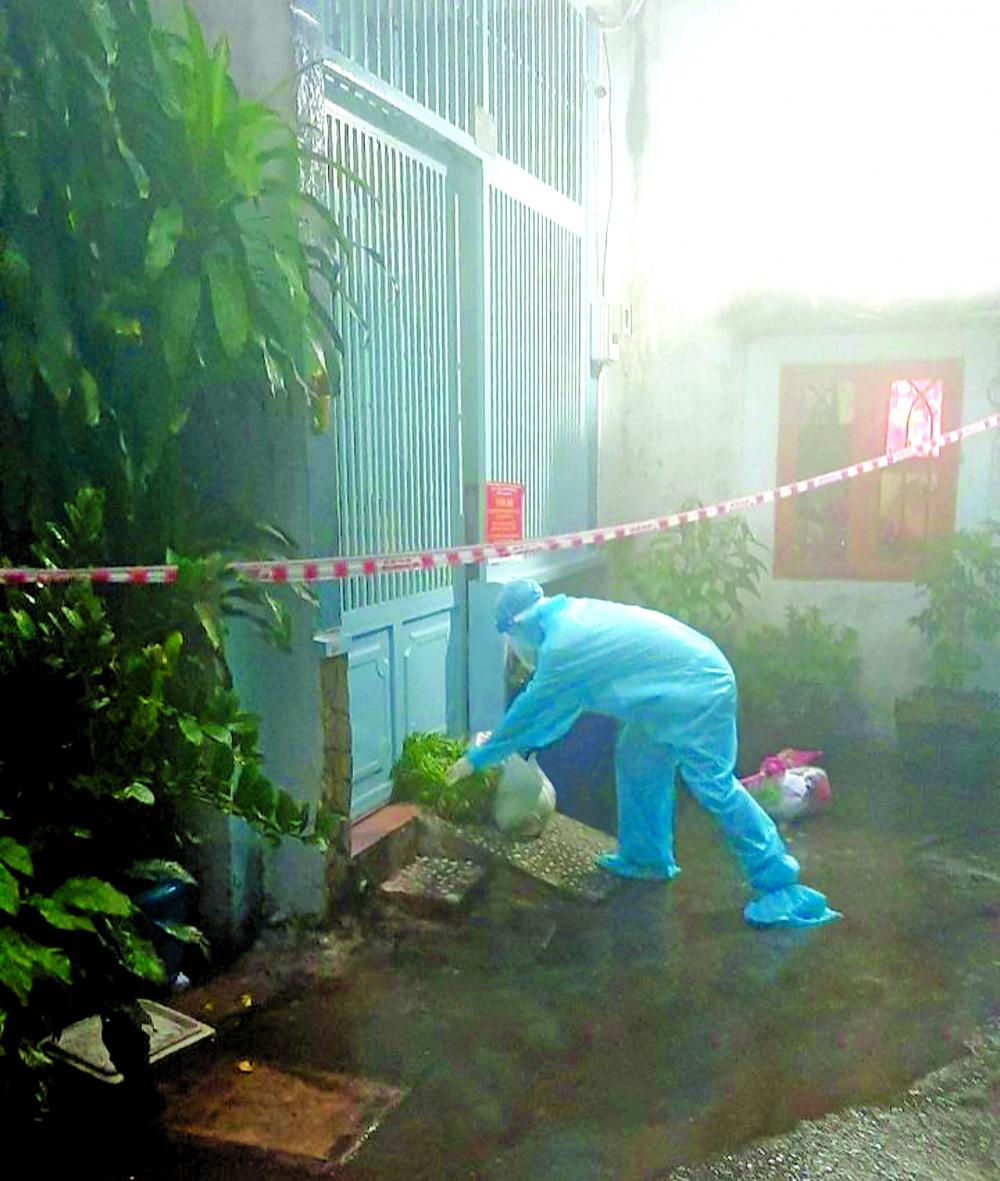 Cán bộ ở phường 10, quận Tân Bình, TP.HCM đội mưa đi đưa thực phẩm cho những trường hợp nhiễm COVID-19 đang cách ly tại nhà - Ả NH: H.C.