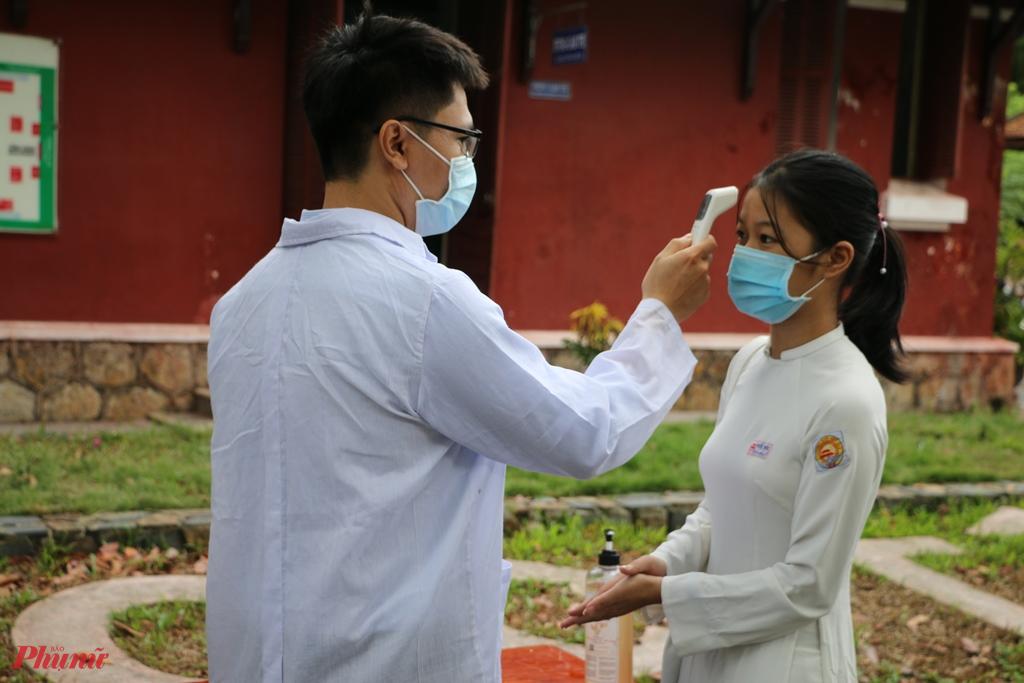 Học sinh được kiểm tra thân nhiệt trước luc vào dự lễ khai giảng tại trươngf THPT Quốc học - Huế