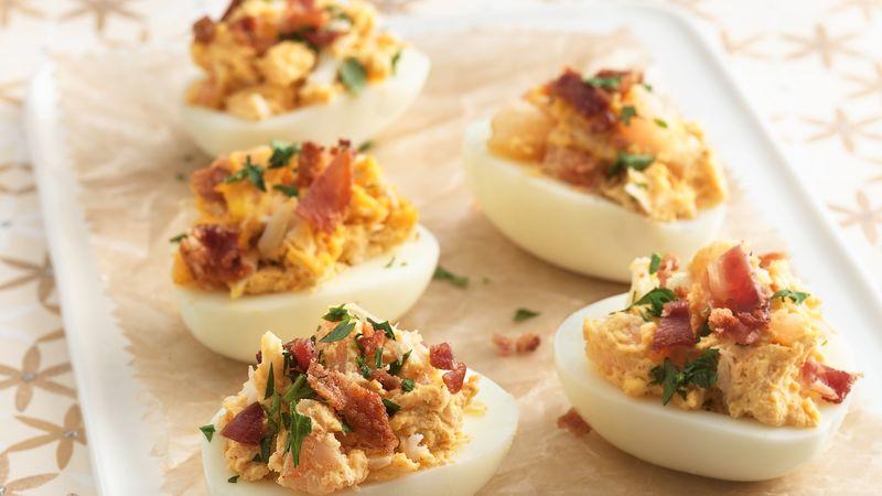 Seafood Deviled Eggs: Thành phần 12 trứng 1/2 chén sốt mayonnaise hoặc sốt salad 1 muỗng cà phê gia vị hải sản (từ hộp 6 oz) 1/2 thìa cà phê ớt bột 1/2 thìa cà phê mù tạt 1/2 chén tôm nấu salad, cắt nhỏ (4 oz) 1 thịt cua đóng hộp (6 oz), để ráo 3 lát thịt xông khói, nấu chín giòn, nghiền nát 2 muỗng canh mùi tây tươi băm nhỏ  Các bước Ngăn màn hình của bạn tối đi khi bạn nấu ăn.  1 Đặt trứng vào lò nướng 4 lít kiểu Hà Lan. Thêm nước lạnh cho đến khi ngập trứng 1 inch. Đun đến sôi; loại bỏ khỏi nhiệt. Đậy nắp và để yên trong 18 phút. Làm lạnh trứng ngay lập tức khoảng 10 phút trong nước lạnh để tránh việc nấu thêm. 2 Vòi trứng để nứt vỏ; lăn trứng giữa hai bàn tay để nới lỏng vỏ, sau đó bóc vỏ. Cắt đôi quả trứng theo chiều dọc. Cho lòng đỏ vào bát vừa; dự trữ một nửa lòng trắng trứng. Nghiền lòng đỏ bằng nĩa. Cho sốt mayonnaise, gia vị, ớt bột và mù tạt xay vào đảo đều cho đến khi hỗn hợp hòa quyện. Cho tôm cua vào xào cùng. 3 Dùng thìa đổ đầy thìa hỗn hợp lòng đỏ vào một nửa lòng trắng trứng. Làm lạnh ít nhất 30 phút trước khi dùng. Ngay trước khi phục vụ, rắc thịt xông khói và mùi tây.