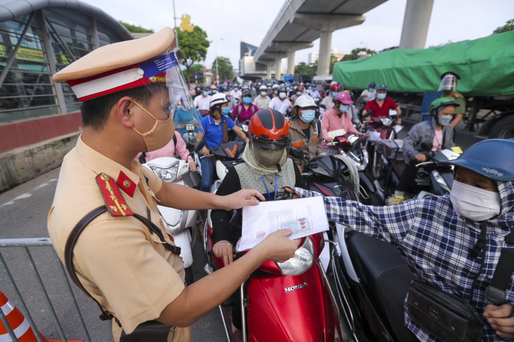 Sáng nay 6-9, người dân Thủ đô bắt đầu ngày làm việc đầu tiên với giấy đi đường được cấp mới cho các nhóm đối tượng được phép di chuyển trong thời gian thực hiện siết chặt giãn cách do Phòng CSGT và công an các xã, phường, thị trấn duyệt cấp.