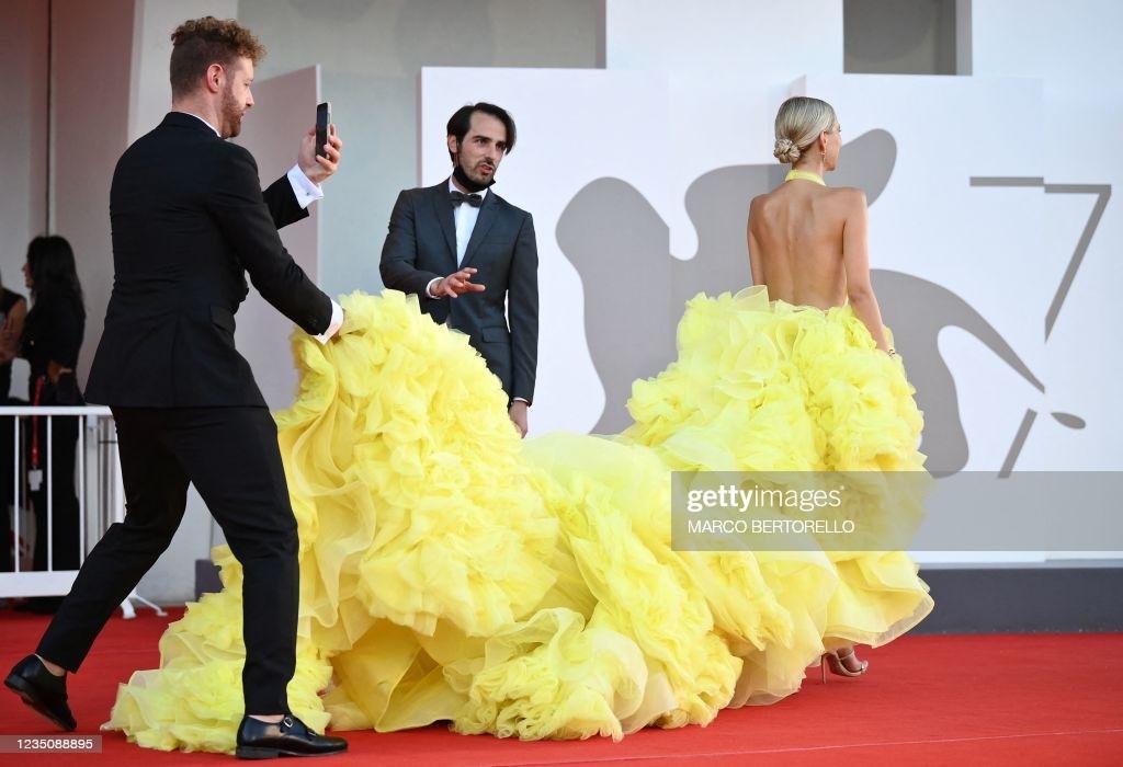 Do bộ váy nặng hàng chục kg nên khi đi thảm đỏ, cô phải nhờ 2 người đàn ông phụ giúp.