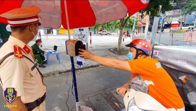 Người dân đi đường đưa mã QR vào camera được gắn tại chốt ngã 6 Phù Đổng, quận 1, để quét mã, ảnh csgt.vn