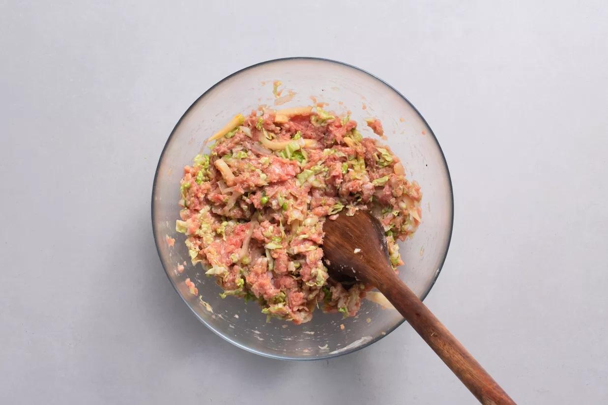 Cho thịt vào tô, thêm  xì dầu , muối, rượu gạo và hạt tiêu. Chỉ khuấy theo một hướng. Cho các nguyên liệu làm nhân còn lại vào trộn đều, đảo theo chiều cho đến khi hỗn hợp kết dính.