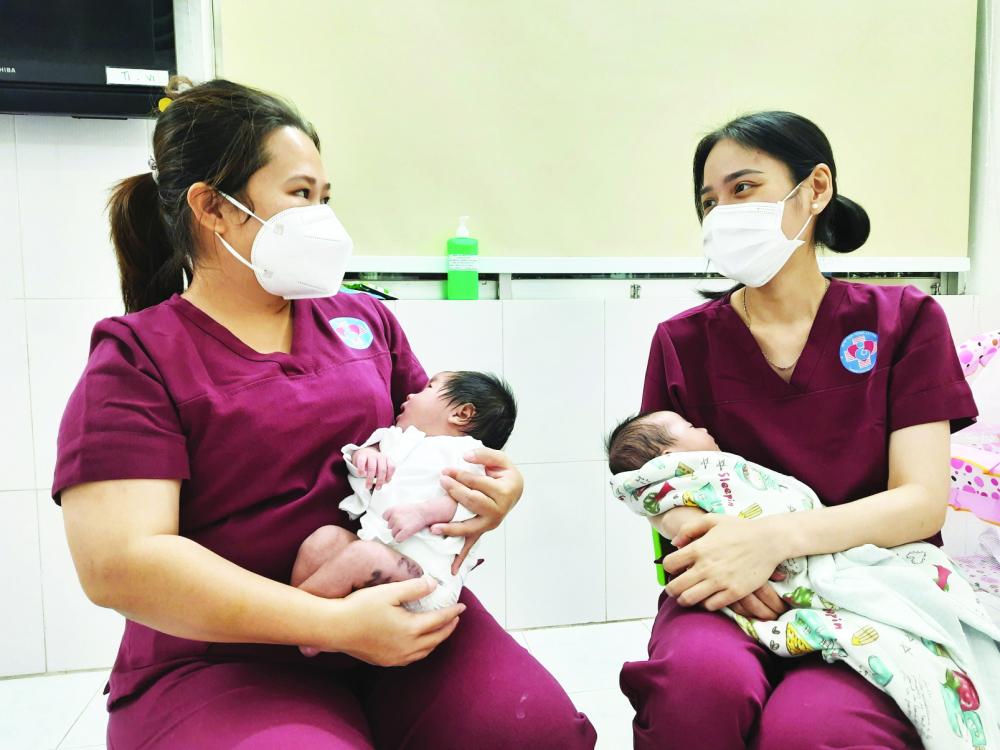 Tình nguyện viên Thanh Phương - Thu Hằng (bên phải) ẵm bé sau khi cho bú