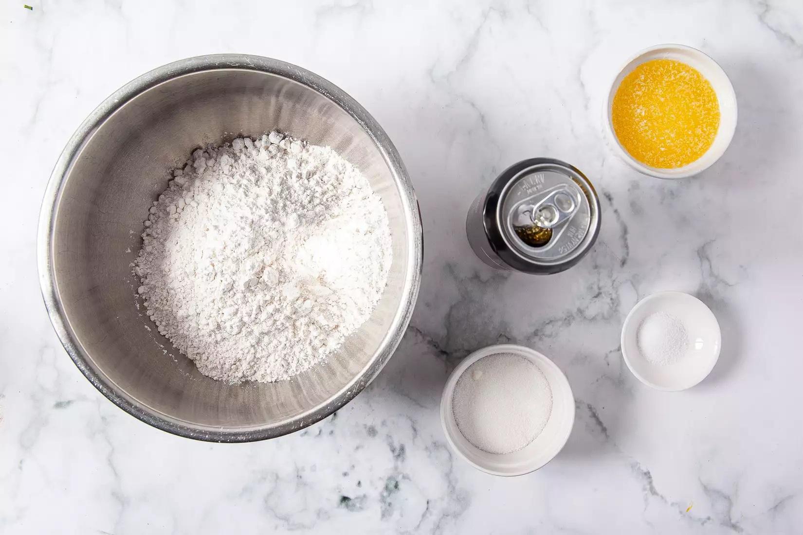 1/2 chén bơ không muối , đun chảy, thêm vào chảo 3 cốc bột mì tự nổi 1/4 cốc đường 1/2 thìa cà phê muối 1 lon bia (12 ounce)