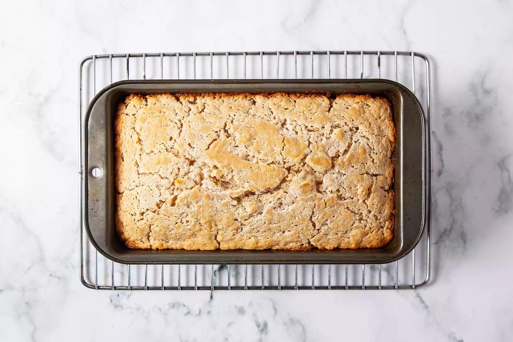 Giữ một giá đỡ dây so với mặt trên của ổ bánh và nhanh chóng, nhưng cẩn thận lật ngược nó xuống để phần trên của ổ bánh nằm ở phía dưới. Đặt sang một bên để làm mát. Điều này sẽ giúp bơ trôi trở lại ổ bánh.