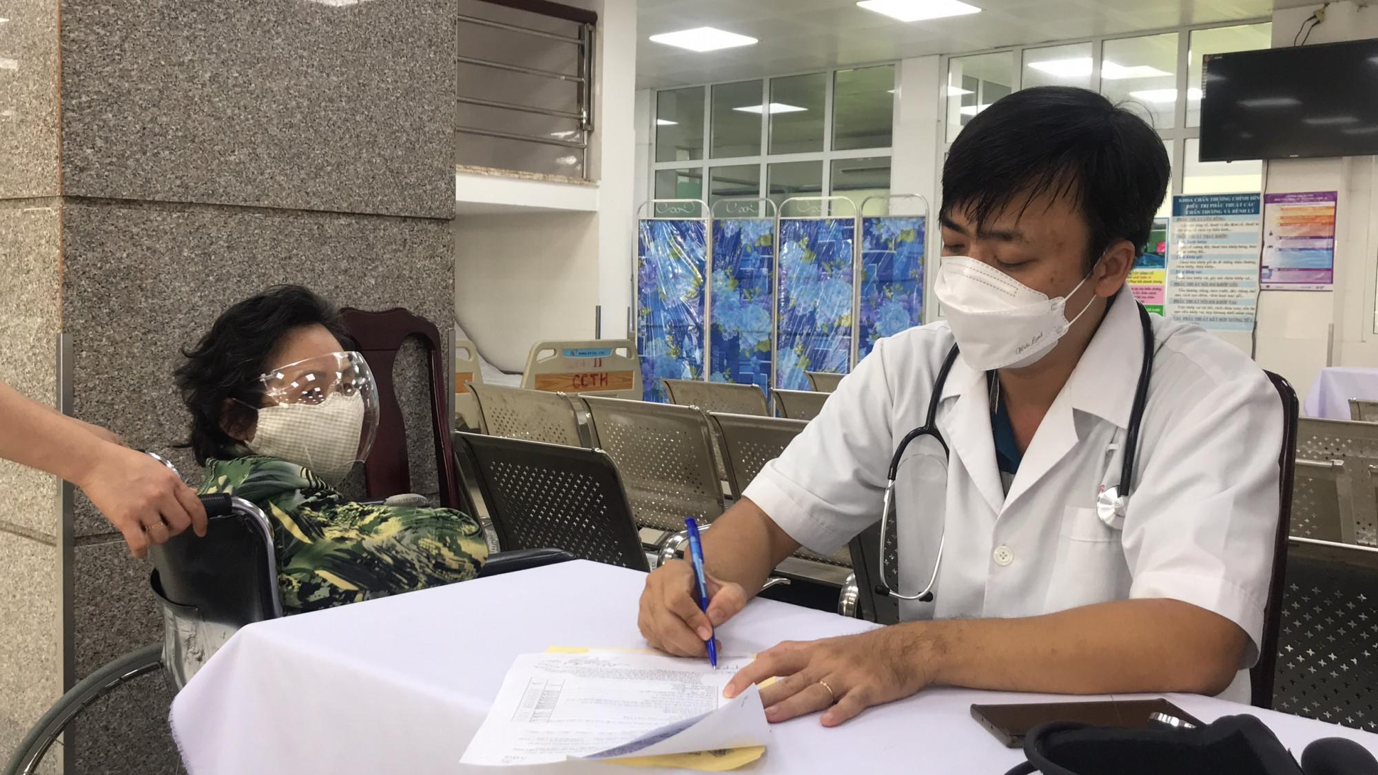 Bác sĩ khám sàng lọc cho một phụ nữ khuyết tật cao tuổi trước khi tiêm vắc xin ngừa COVID-19