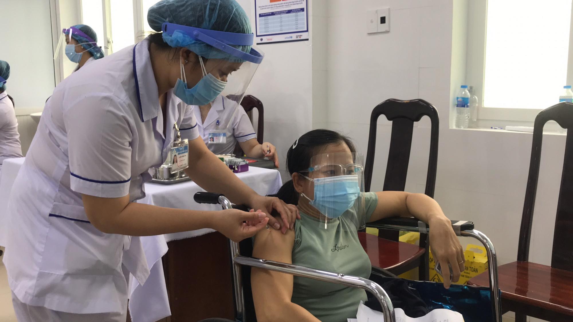 Y bác sĩ tiêm vắc xin ngừa COVID-19 cho một phụ nữ không may bị khuyết tật