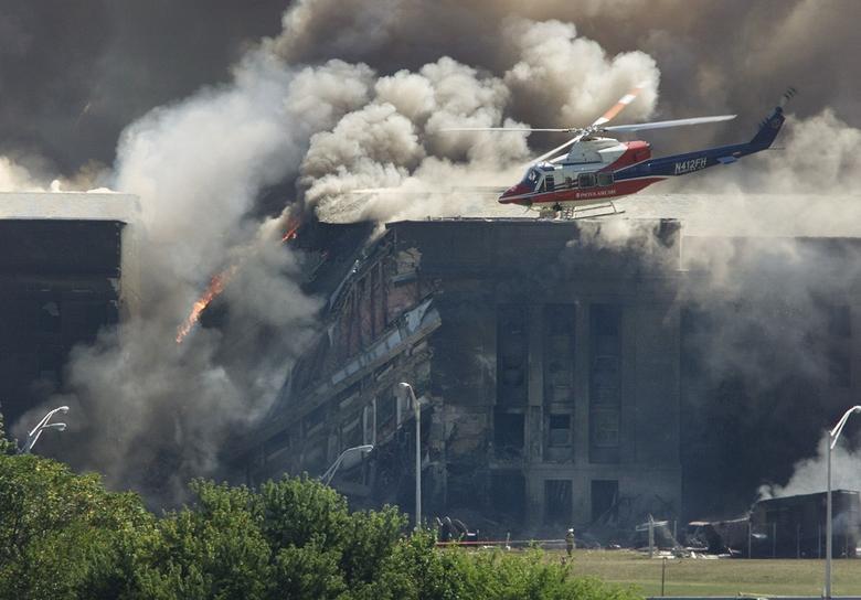 Một máy bay trực thăng cứu hộ khảo sát thiệt hại tại Lầu Năm Góc, còn các nhân viên cứu hỏa chiến đấu với ngọn lửa sau khi một máy bay bị cướp đâm vào trụ sở quân đội Mỹ bên ngoài Washington. (Ảnh: Reuters)