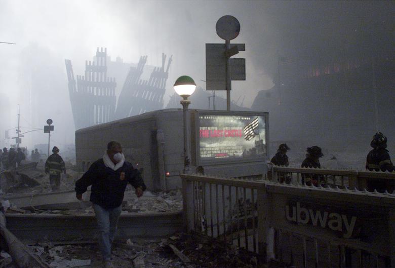 Một người đàn ông đi qua trạm dừng tàu điện ngầm gần khu vực số 0 - hiện trường vụ tấn công hai tòa tháp. Đống đổ nát của Trung tâm Thương mại Thế giới cháy âm ỉ khi (Ảnh: Reuters)