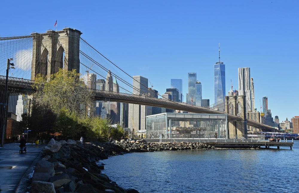 """Ảnh chụp màn hình từ bộ phim """"Saturday Night Fever"""" năm 1977 cho thấy Cầu Brooklyn bắc qua Sông Đông và tòa tháp đôi của Trung tâm Thương mại Thế giới dọc theo đường chân trời của Manhattan (ảnh trên). Quang cảnh Cầu Brooklyn với đường chân trời của Manhattan, bao gồm cả Trung tâm Thương mại Một Thế giới, được chụp vào ngày 16/11/2018. (Ảnh: Getty Images)"""