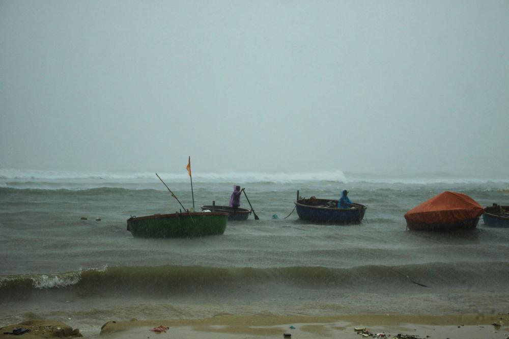 Ngư dân bơi ra biển để buộc thúng phòng chống bão số 5