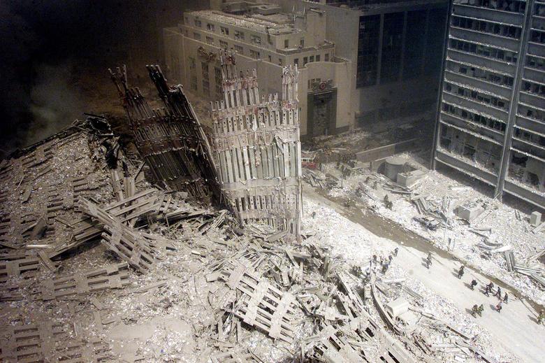Một nhóm lính cứu hỏa đi bộ giữa đống đổ nát gần chân tháp Nam bị phá hủy của Trung tâm Thương mại Thế giới ở New York. (Ảnh: Reuters)