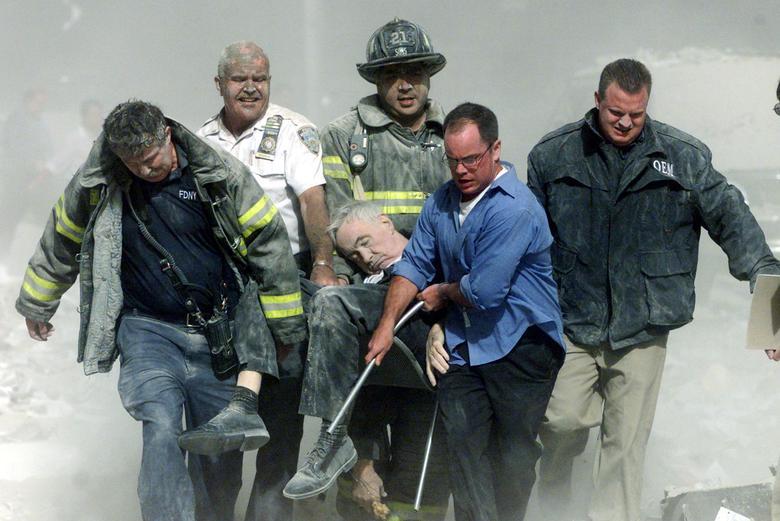Các nhân viên cứu hộ khiêng Rev. Mychal Judge, Sở Cứu hỏa Thành phố New York, bị thương nặng từ đống đổ nát của Trung tâm Thương mại Thế giới. Vị tuyên úy đã bị đè chết do các mảnh vỡ rơi xuống khi đang thực hiện nghi thức cầu nguyện cuối cùng cho một người đàn ông ở trung tâm thương mại - Ảnh: Reuters