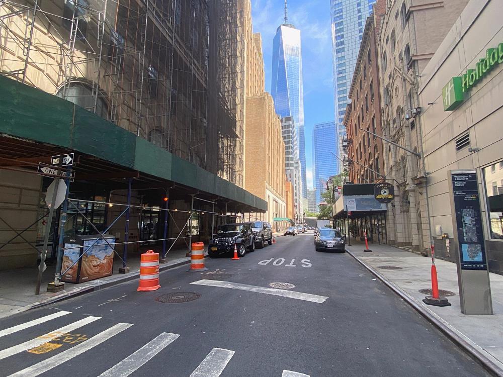 Bụi và mảnh vỡ bao phủ mặt đất và tao ra làn mây mù bao trùm Phố Washington, cách khu vực số 0 vài tòa nhà, trong những ngày sau vụ tấn công 11/9 (ảnh trên - AP). Cũng con phố đó vào ngày 15/8/2021, với tầm nhìn trực diện ra Trung tâm Thương mại Một Thế giới (Ảnh: PIX11).