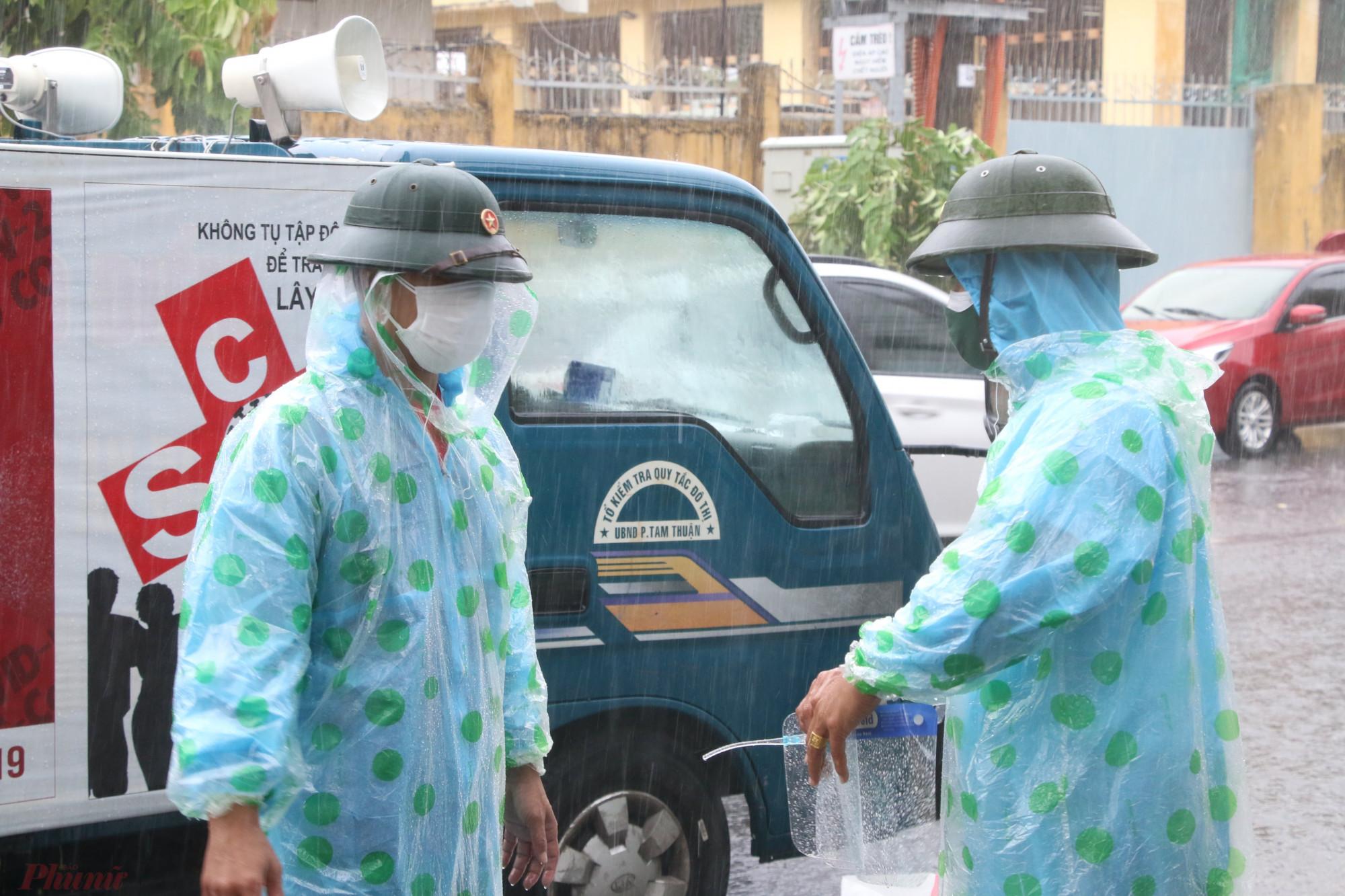 Thực thi nhiệm vụ dưới trời mưa bão gió nhưng do dịch bệnh diễn biến đang phức tạp nên các chiến sỹ vẫn phải đảm bảo trang bị bảo hộ phòng chống dịch
