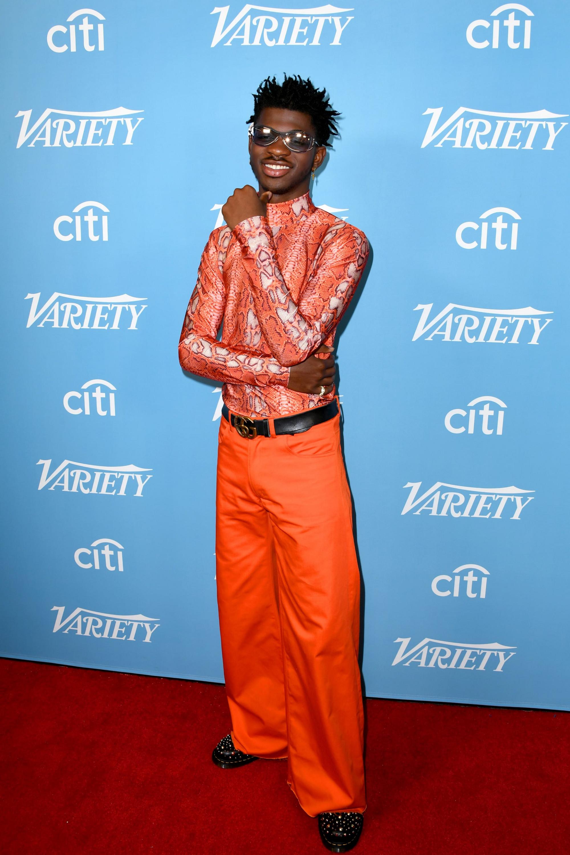 Chiếc áo ôm hoạ tiết da trăn kết hợp với quần ống loe màu cam được xem là trang phục tương đóinhã nhặn của nam ca sĩ khi xuất hiện trước đám đông.