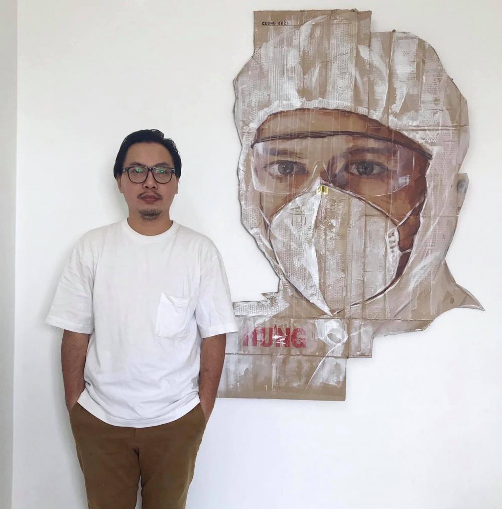 Họa sĩ Nguyễn Việt Cường và tác phẩm 'Doctor' được vẽ trên nhiều tấm carton ghép lại.