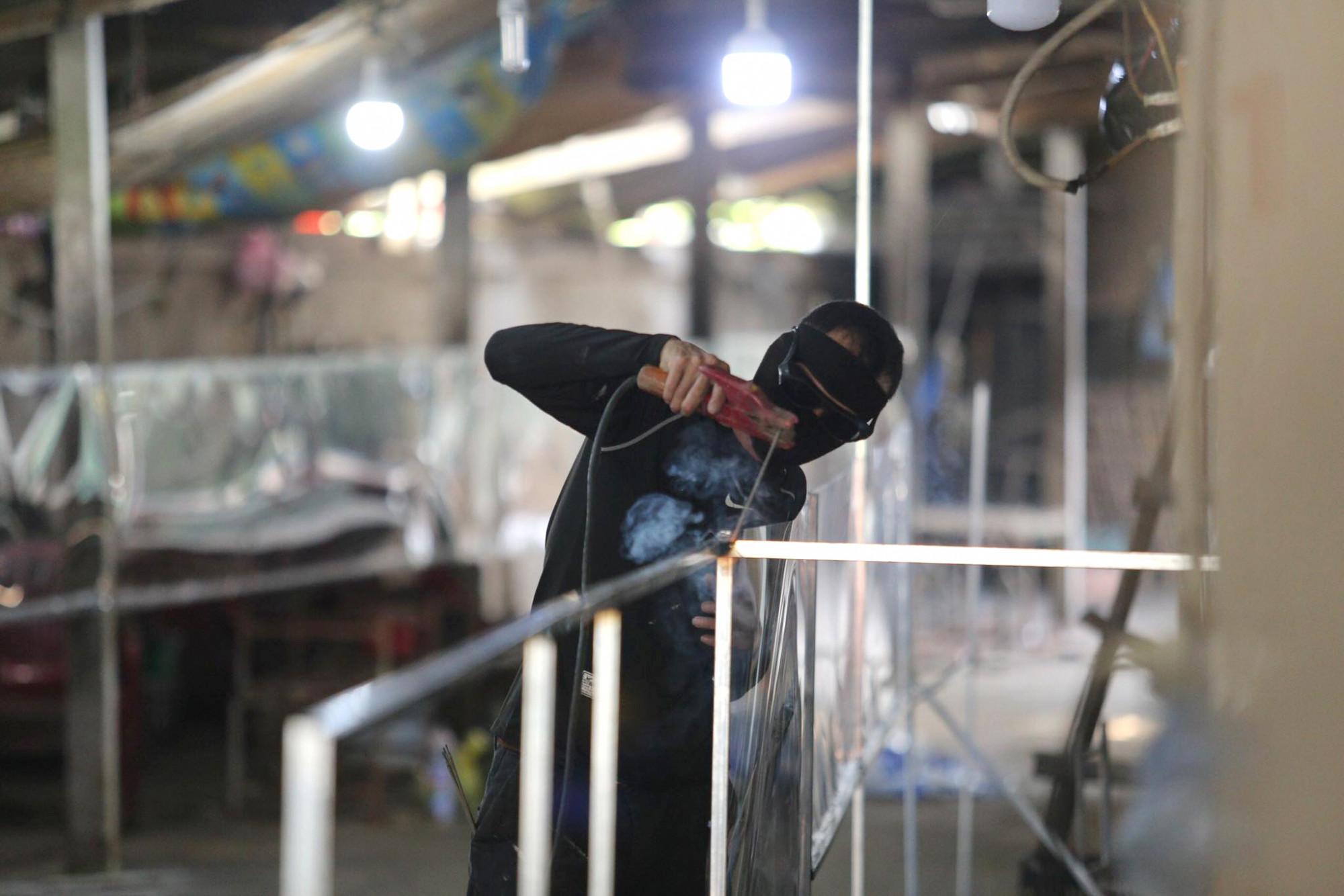 Thợ hàn cũng được tiểu thương thuê đến để lắp đặt các tấm chống bắn, che chắn trước khu vực bán hàng, hạn chế tiếp xúc...