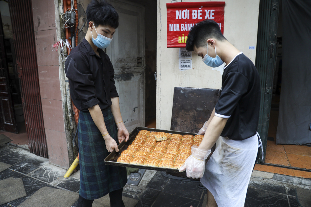 Nhân viên cửa hàng luôn tay mang những mẻ bánh mới sang khu vực đóng hộp trước khi đem bán cho khách.