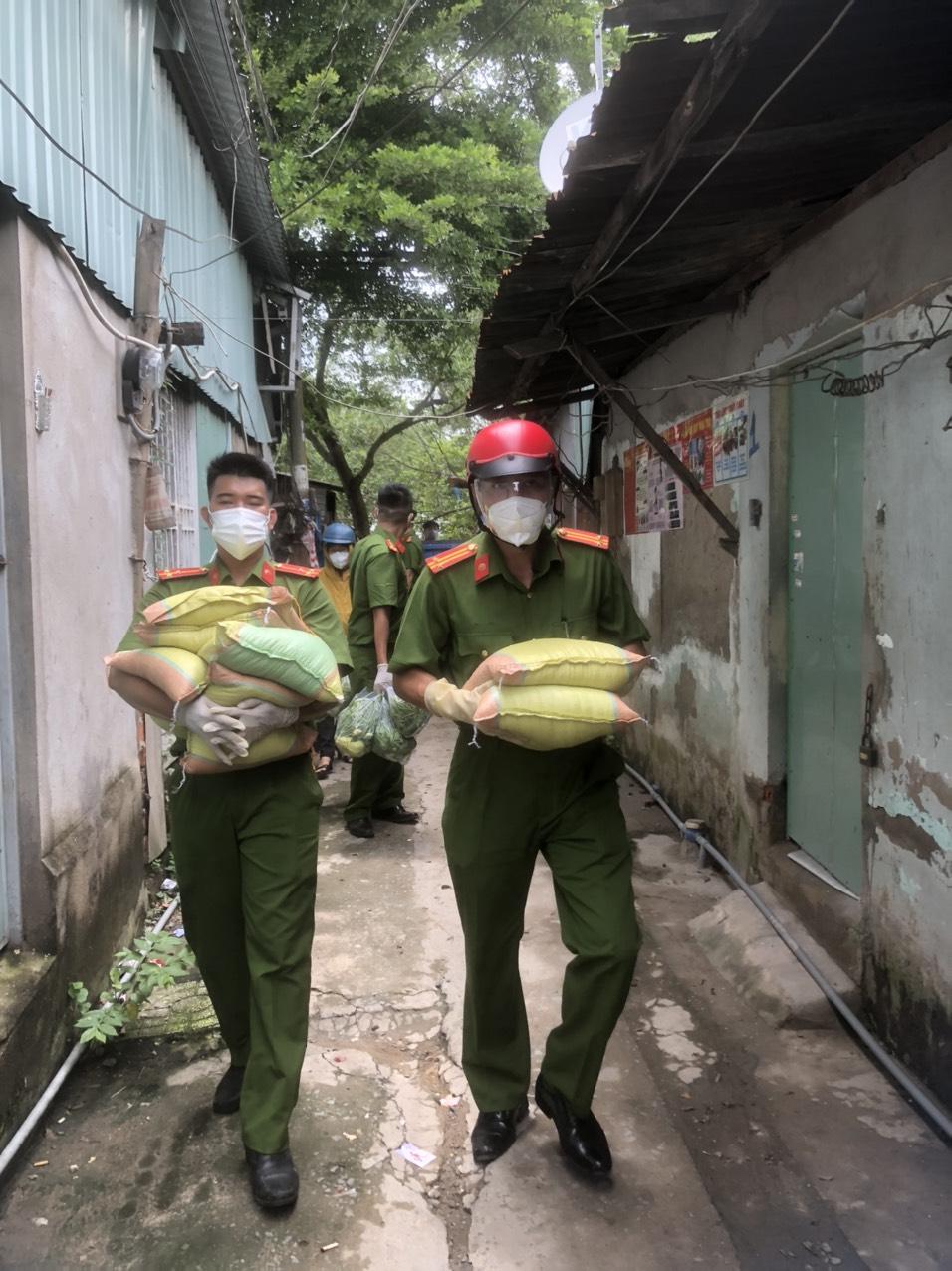 """Phòng Cảnh sát hình sự (PC02), Công an TPHCM (hay còn gọi là """"Quả đám thép"""") bê từng bao gạo, bó rau… tới trao những phần quà cho người dân nghèo, hoàn cảnh khó khăn ở xã Bình Hưng, huyện Bình Chánh."""