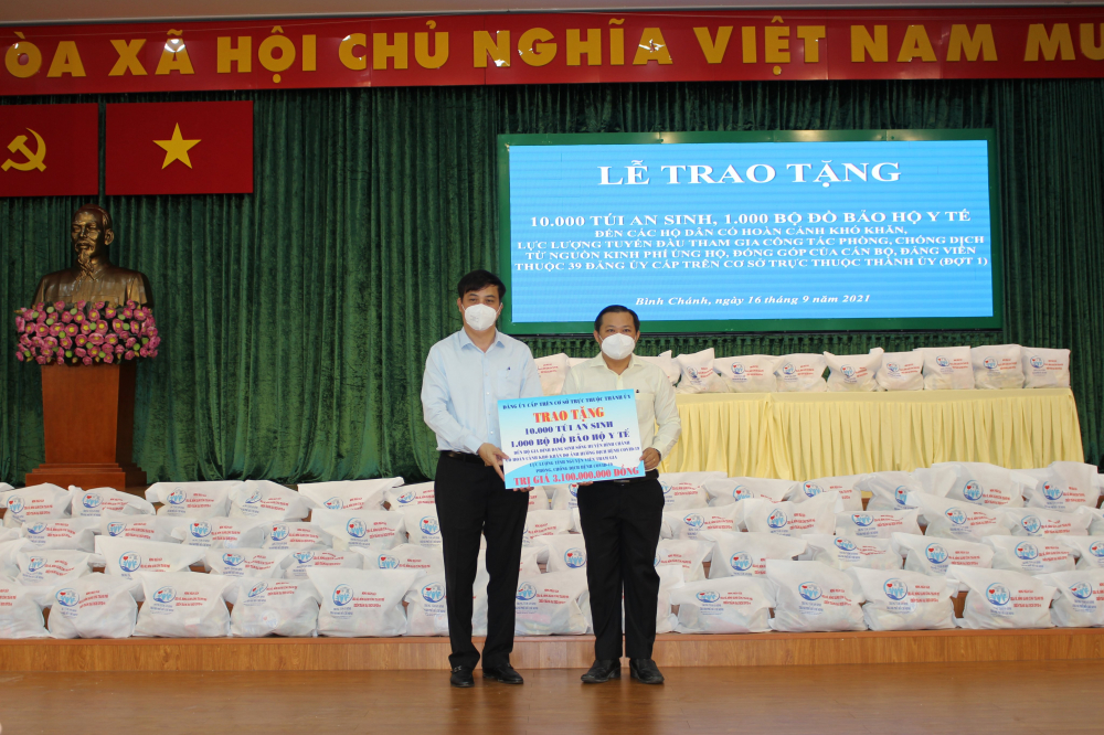 Phó Chủ tịch UBND Thành phố Lê Hòa Bình trao tặng 10.000 túi an sinh, 1.000 bộ đồ bảo hộ y tế đến hộ gia đình khó khăn; lực lượng tham gia phòng, chống dịch H.Bình Chánh (bảng biểu trưng).