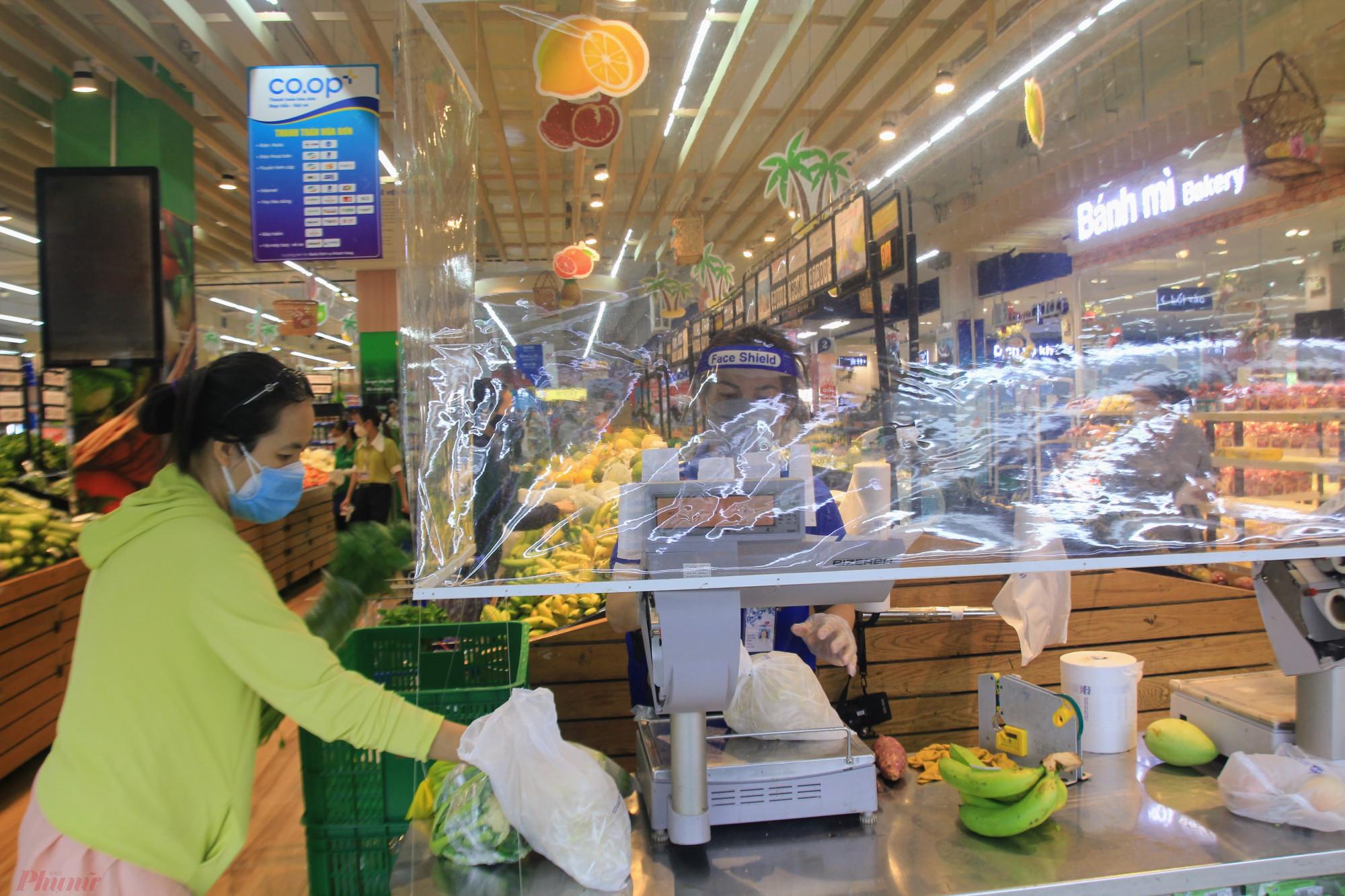 Tại một số khu vực cân thực phẩm, tính tiền siêu thị này đều lắp vách ngăn hạn chế tiếp xúc giữa khách hàng và nhân viên siêu thj.