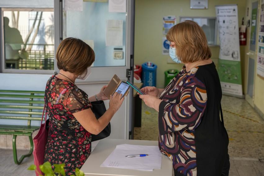 Một giáo viên xuất trình thẻ xanh cho nhân viên kiểm tra trước khi vào trường ở Rome.