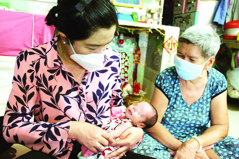 Bà Nguyễn Trần Phượng Trân - Chủ tịch Hội LHPN TP.HCM - thăm bé chín ngày tuổi mất mẹ do COVID-19 ở H.Bình Chánh