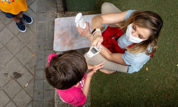 Một đứa trẻ được kiểm tra thân nhiệt trước khi vào trường mầm non ở Tây Ban Nha. Năm triệu chứng Covid kéo dài phổ biến nhất được báo cáo ở trẻ em và thanh thiếu niên là nhức đầu, mệt mỏi, rối loạn giấc ngủ, khó tập trung và đau bụng. Ảnh: Pablo Cuadra / Getty Images