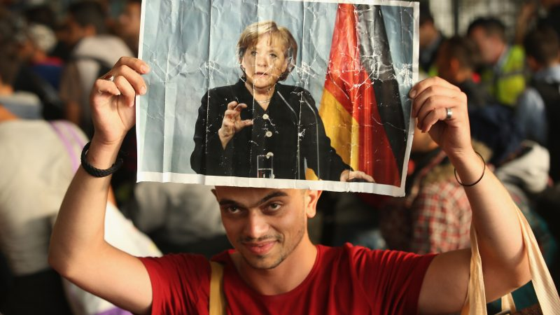 Một thanh niên tị nạn người Syria với tấm ảnh Thủ tướng Angela Merkel tháng 5/2015 - Ảnh: Sean Gallup/Getty Images