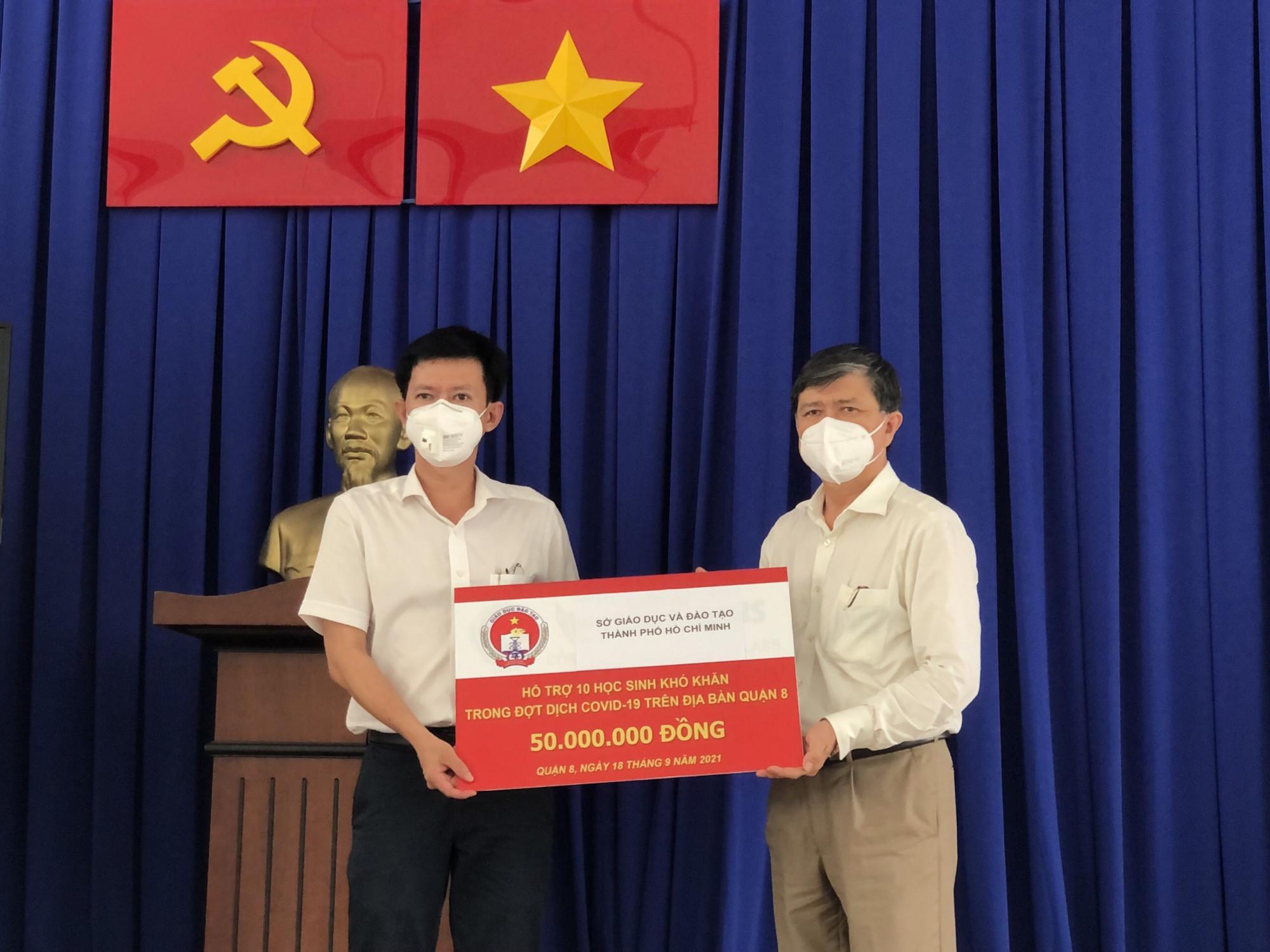 Ông Nguyễn Văn Hiếu, Giám đốc Sở GT-ĐT TPHCM (phải) trao học bổng cho đại diện Phòng GD-ĐT quận 8