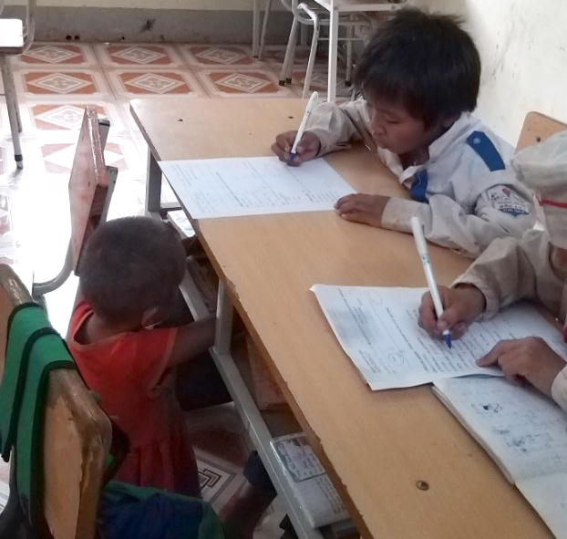 Cảnh anh chị học bài, em ngồi chơi đùa bên cạnh không quá xa lạ ở Trường Phổ thông dân tộc bán trú tiểu học Bắc Lý 1