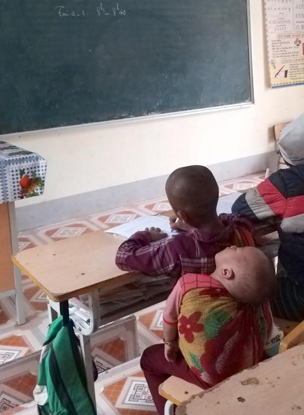 Một học sinh lớp 1 say sưa học bài khi em đang say giấc ngủ trên lưng