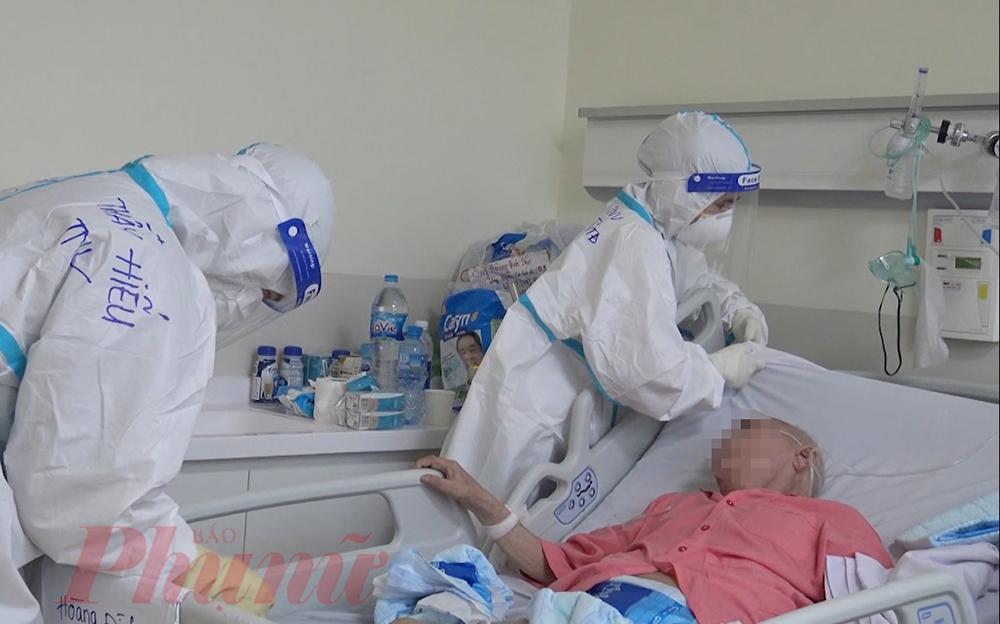Chị Vũ Thị Mai Thoa cùng các tình nguyện viên thay ga trải giường, vệ sinh cá nhân cho một ông cụ mắc bệnh. Hơn 20 ngày qua, cụ chưa từng nhìn thấy rõ mặt của người chăm sóc mình, nhưng sự chu đáo của các anh chị luôn làm cho bệnh nhân có thêm nhiều động lực trở về với con cháu của mình