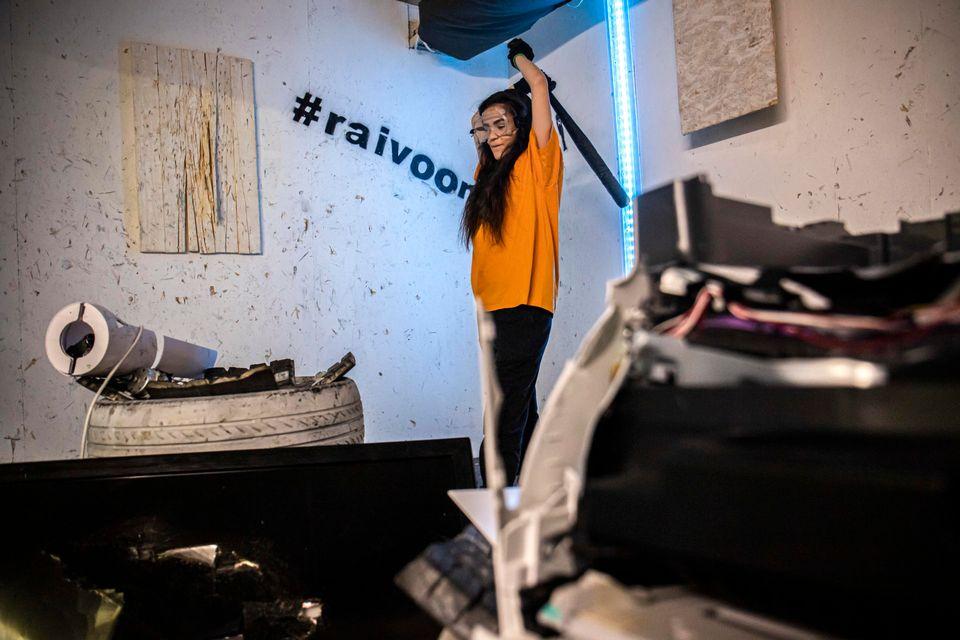 Một cô gái đang đập phá đồ đạc bên trong căn phòng trút giận ở Phần Lan - Ảnh: Matti Myller/Yle