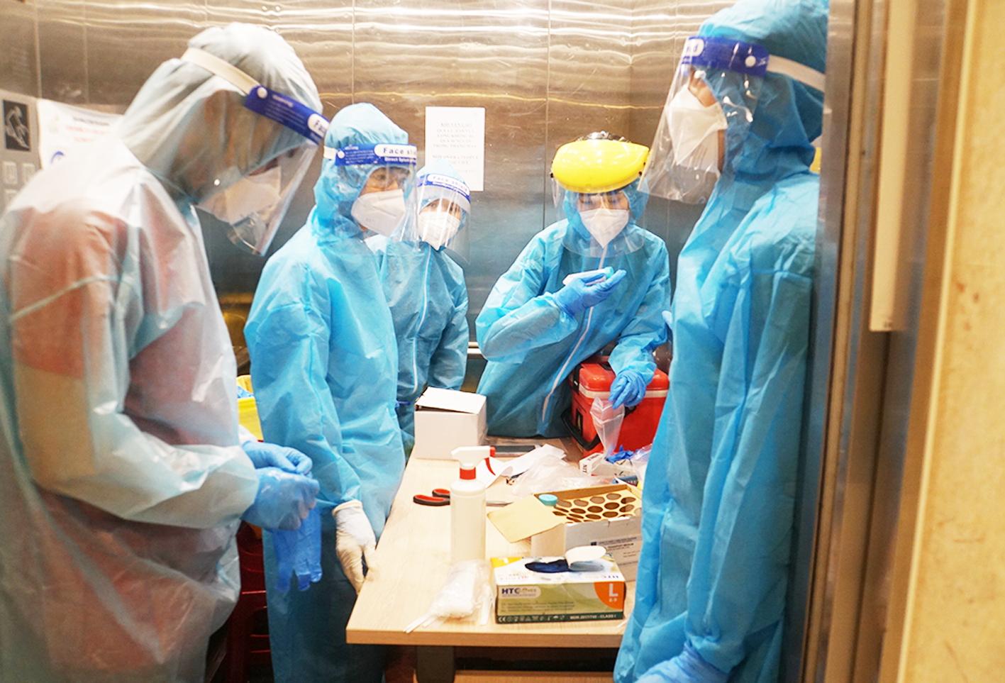 Anh Nguyễn Lê Hoàng (thứ hai từ trái qua) cùng đoàn bác sĩ của Trạm y tế P.1, Q.4 đến từng nhà xét nghiệm COVID-19 ẢNH: PHẠM AN