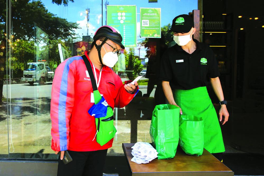 Shipper lấy hàng ở một quán cà phê trên đường Lê Văn Lương (Q.7, TP.HCM) ẢNH: LINH LINH