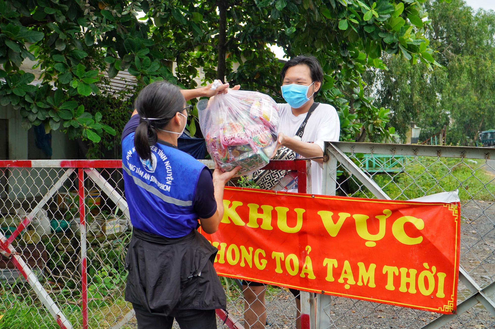 Tình nguyện viên đội SOS giao túi an sinh trực tiếp cho người dân khó khăn